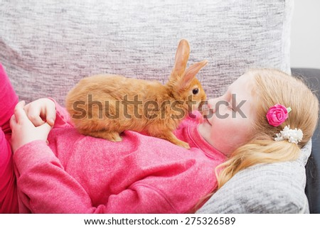 smiling girl  with  rabbit indoor - stock photo