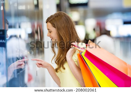 Smiling girl with shopping bags in shopping mall - stock photo