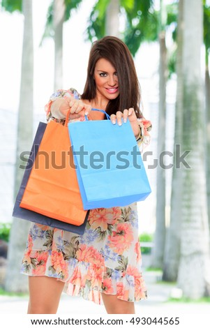Smiling girl with shopping bags in the street