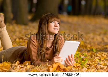 Smiling girl with tablet pc on the autumn landscape, outdoors - stock photo