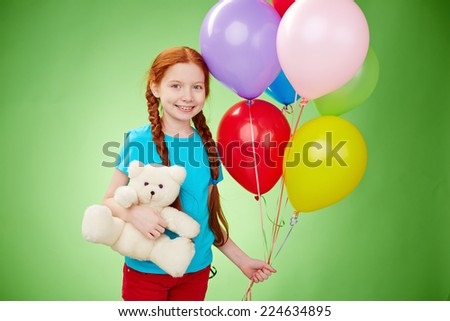 Smiling girl with teddybear and balloons looking at camera - stock photo