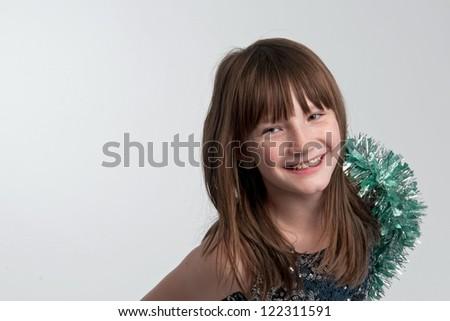 Smiling girl with tinsel, studio shot - stock photo
