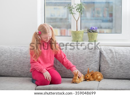 smiling girl with two rabbits indoor - stock photo