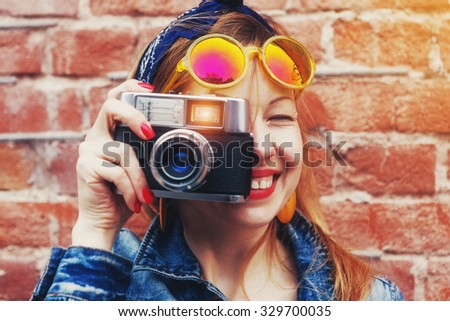 smiling girl with vintage camera taking photo with flash on brick wall background - stock photo