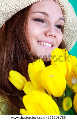 Smiling girl with yellow tulips over green background - stock photo
