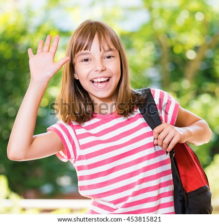 Smiling girl 10-11 year old stretching her right hand up for greeting .Beautiful schoolgirl with backpack posing outdoors. - stock photo