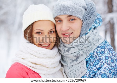 Smiling girlfriend and boyfriend in winterwear looking at camera - stock photo