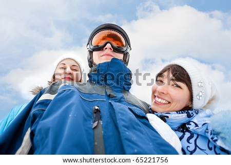 Smiling girls in blue embrase man in sky mask