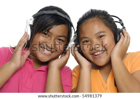 Smiling girls listening to music on headphones isolated over white - stock photo