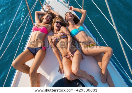 Smiling girls lying on yacht. Sexy ladies in swimsuits. Can't stop laughing. Summer holidays you'll never forget. - stock photo