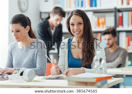 Smiling girls sitting at desk and studying in the classroom, learning and education concept