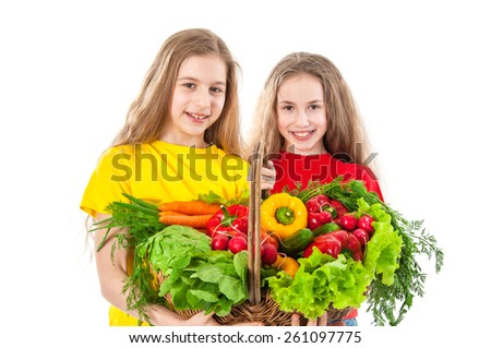 Smiling girls with basket of vegetables - stock photo