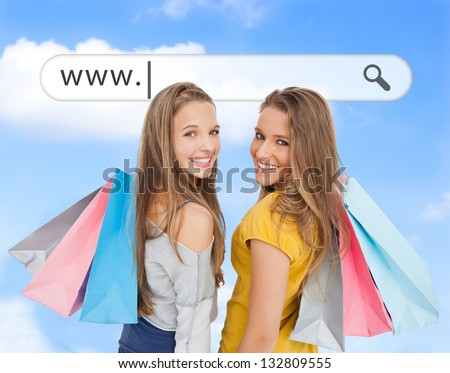 Smiling girls with their shopping bags under address bar on blue sky background - stock photo