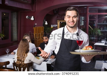 Smiling glad young waiter taking care of adults at cafe table