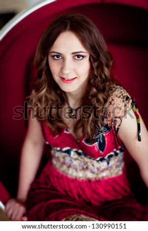 Smiling glamorous girl in a light dress sitting in a chair ball