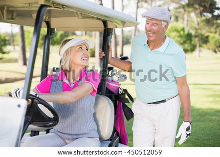 Smiling golfer woman looking at man while sitting in golf buggy - stock photo