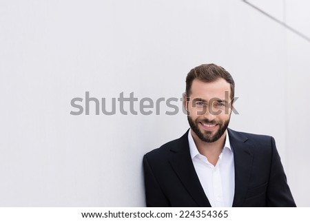 Smiling Good Looking Middle Age Man in Black and White Suit Leaning on White Wall. - stock photo