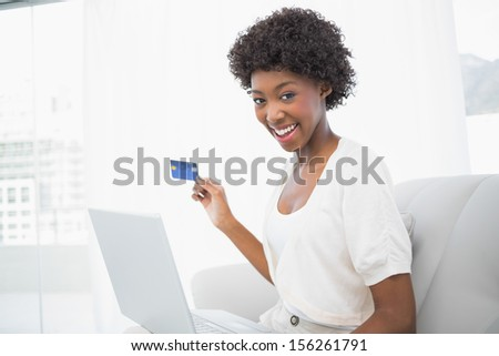 Smiling gorgeous brunette using her credit card to buy online sitting on cosy sofa - stock photo