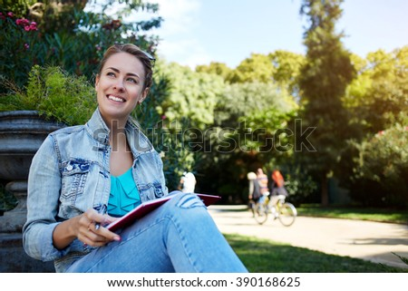 Smiling gorgeous female is enjoying free time and rest during her long awaited sparing weekend, happy cheerful hipster girl with good mood is sitting with notepad in beautiful park during leisure - stock photo