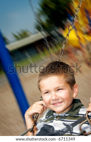 Smiling grade school student plays on a swing set during recess