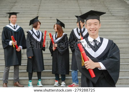 Smiling graduates posing holding their diploma in front of the university - stock photo
