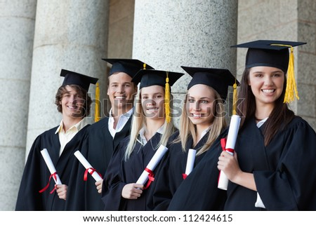 Smiling graduates posing in single line with columns in background - stock photo