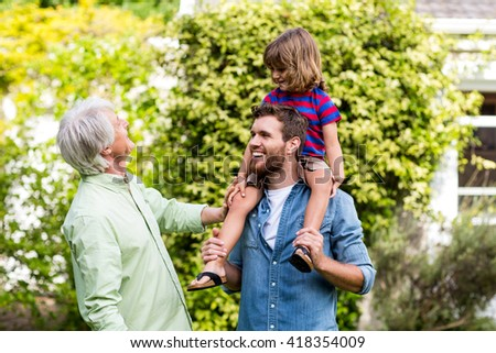 Smiling granddad looking at son carrying grandson in yard - stock photo