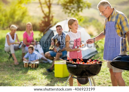 smiling granddaughter baking barbecue with grandfather on camping