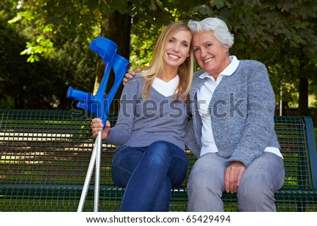 Smiling granddaughter with handicapped grandmother on park bench - stock photo