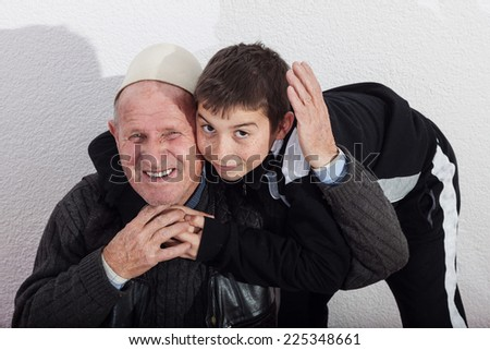 smiling grandfather embracing nephew - stock photo