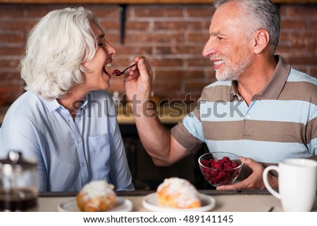 Smiling grandfather feeding grandmother with a tea-spoon
