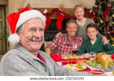 Smiling grandfather in santa hat posing in front of his family at home in the living room - stock photo