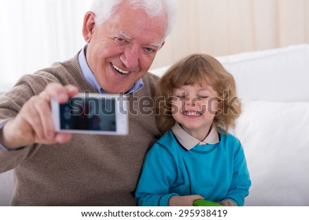 Smiling grandfather with grandson taking photo by mobile phone - stock photo