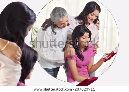 Smiling grandmother and mother gifting jewelry to the girl - stock photo