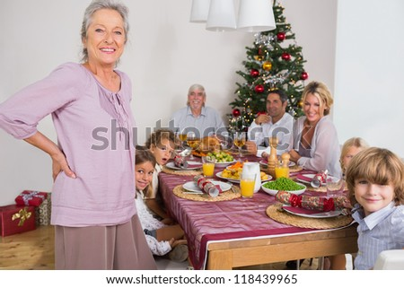 Smiling grandmother standing beside dinner table at christmas - stock photo