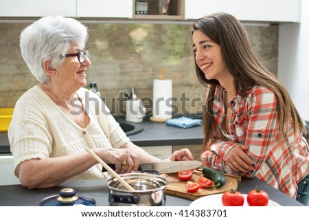 Smiling grandmother with granddaughter cooking in the kitchen. - stock photo