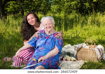 Smiling grandmother with granddaughter resting in the park - stock photo