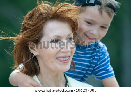 Smiling grandmother with grandson on a green background - stock photo