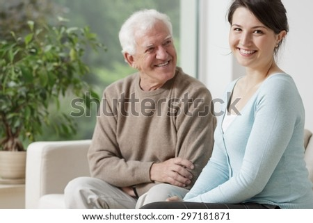 Smiling grandpa and caring granddaughter at home - stock photo