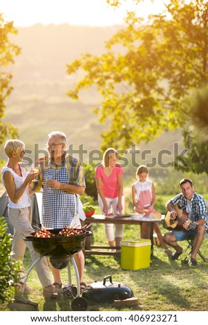 smiling grandparents drinking wine and enjoying picnic with family - stock photo
