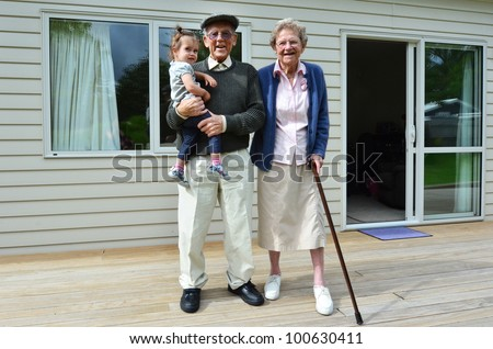 Smiling grandparents holding their grandchild outside their home.Concept photo of grandparents, grandfather, grandad, ,grandchild, childhood, granddaughter, relationship, lifestyle,family, education.