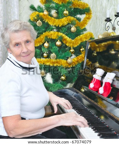 smiling granny play to piano Christmas song - stock photo