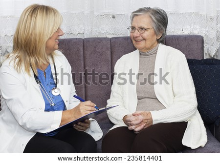 Smiling gray hair grandmother with crossed fingers sitting on the sofa and talking with her mature female doctor at home. - stock photo