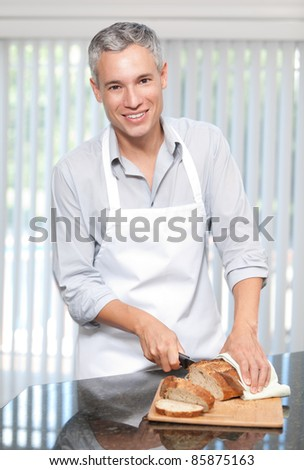 Smiling grey hair man cutting bread in apron
