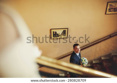 smiling groom is going up stairs and holding bouquet - stock photo