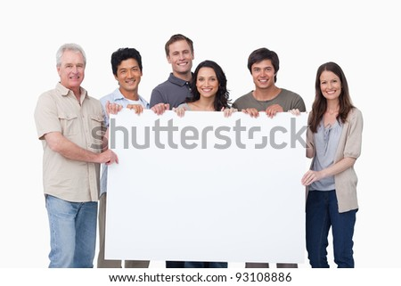 Smiling group holding blank sign together against a white background - stock photo