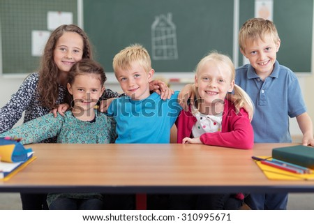 Smiling group of classmates in primary school posing arm in arm behind a desk grinning happily at the camera, boys and girls