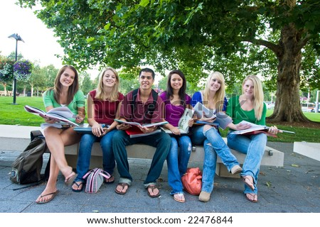 Smiling group of five high school girls and one boy sitting on a bench holding books. Horizontally framed photo. - stock photo