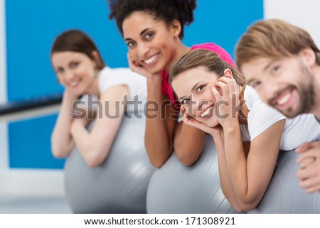 Smiling group of friends practicing Pilates at the gym working out with silver gym balls with focus to a pretty young women with her hands to her face - stock photo