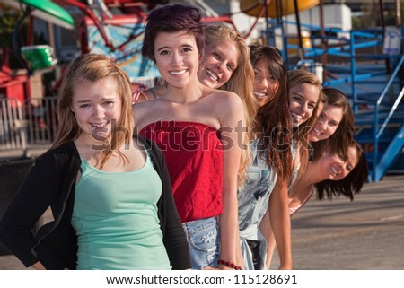 Smiling group of teenage girls standing behind each other - stock photo